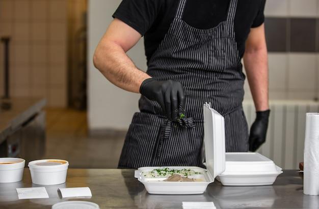 Chefkoch bereitet gericht zu einer kiste im restaurant für lebensmittel-lieferservice nach hause vor, online-bestellung