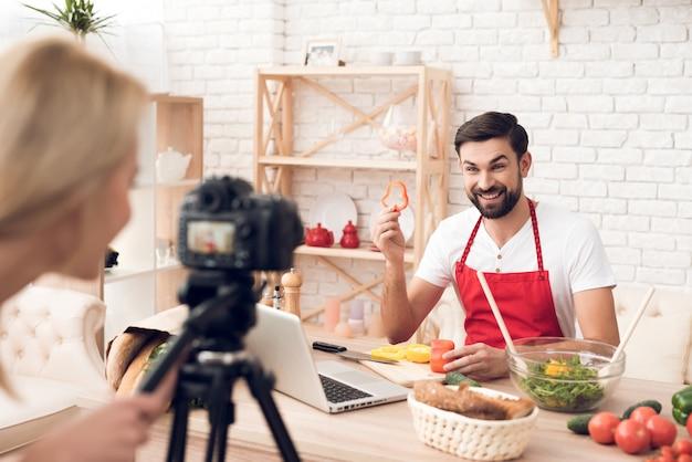 Chefkoch bereitet lebensmittelzutaten für kulinarische podcst-zuschauer zu.