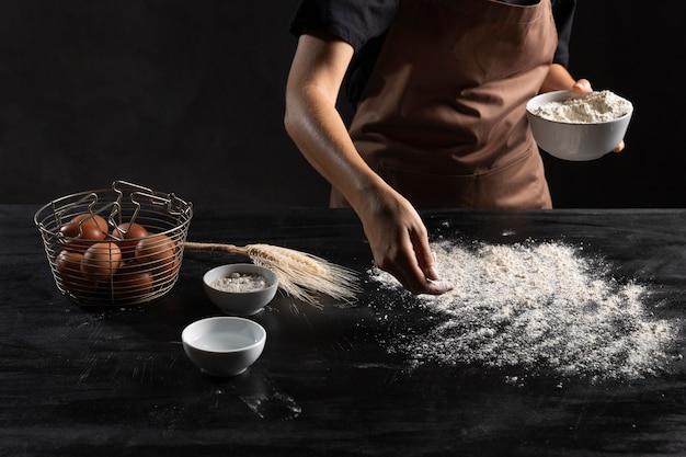 Chefkoch bestäubt den tisch mit mehl zum kneten des teigs