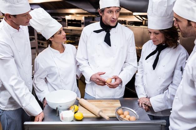 Chefkoch bringt seinem team bei, einen teig zuzubereiten