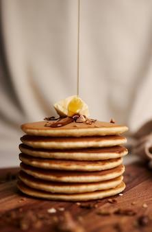 Chefkoch, der ahornsirup auf einen stapel köstlicher pfannkuchen gießt