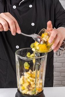 Chefkoch, der dem mixer früchte hinzufügt