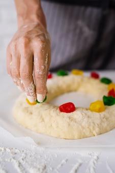 Chefkoch, der dreikönigstagsdessert mit süßer süßigkeit vorbereitet