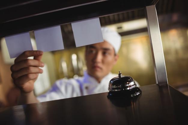 Chefkoch, der eine bestellliste in der gewerblichen küche betrachtet