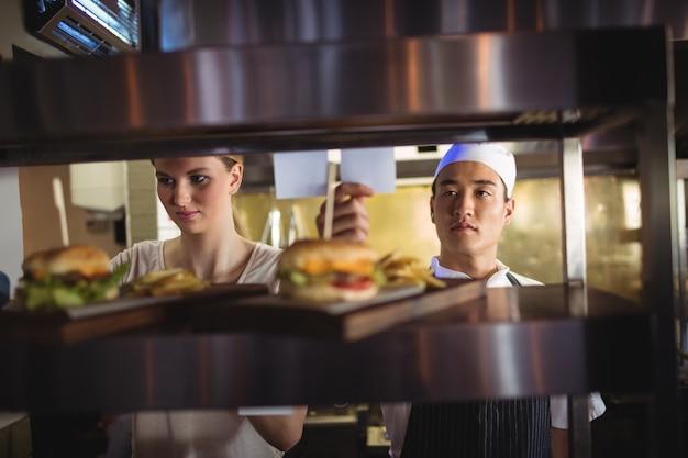 Chefkoch, der eine bestellliste in der küche betrachtet