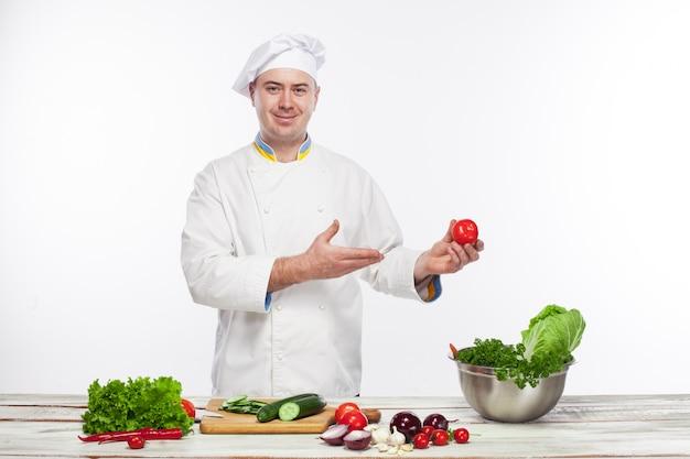 Chefkoch, der frischen gemüsesalat in seiner küche kocht