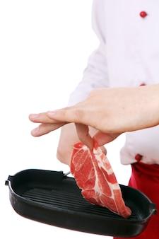 Chefkoch, der frisches fleisch auf eine pfanne legt