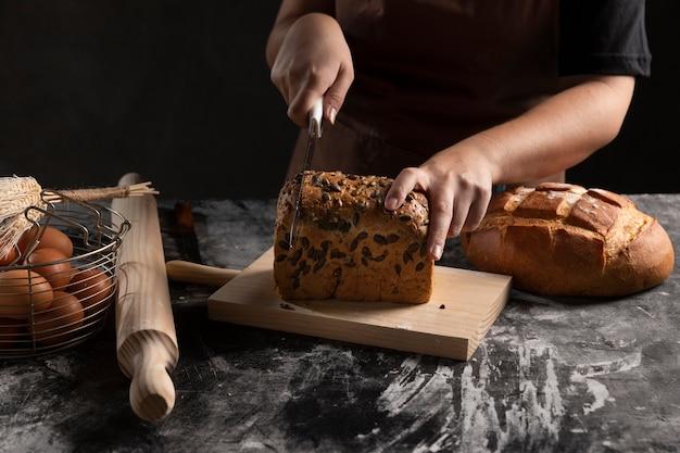 Chefkoch, der gebackenes brot auf schneidebrett schneidet