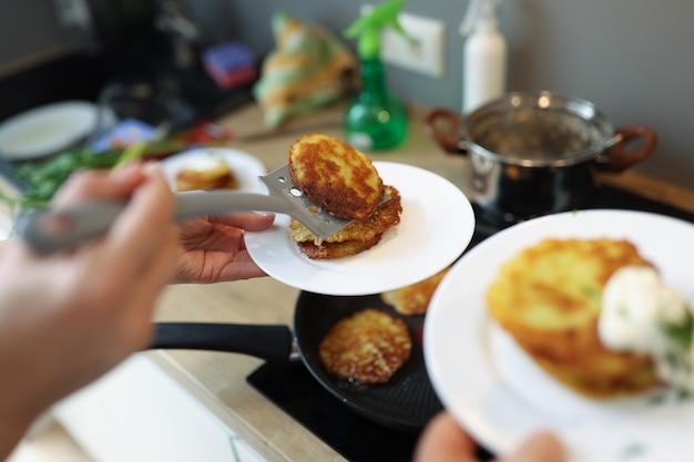 Chefkoch, der gebratene kartoffelpfannkuchen in der bratpfannenahaufnahme zubereitet. konzept der kartoffelrezepte