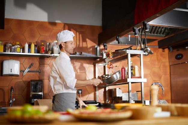 Chefkoch, der gemüse in der restaurantküche kocht