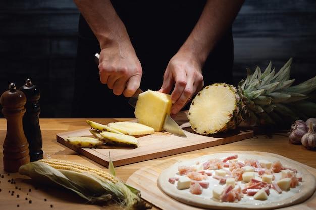 Chefkoch, der hawaiianische pizza kocht und frische ananas schneidet
