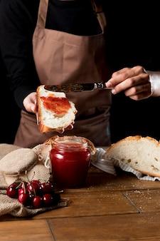 Chefkoch, der kirschmarmelade auf brot verteilt