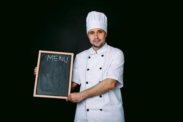 Chefkoch, der kochjacke und hut trägt und eine piazarra mit menü hält, auf schwarzem hintergrund