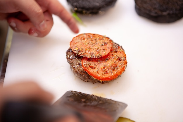 Chefkoch, der köstliches burgerfleisch zubereitet. im restaurant