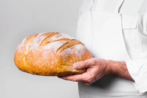 Chefkoch, der köstliches gebackenes brot hält