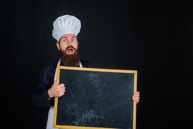 Chefkoch, der leere menütafel mit kopienraum zeigt lächelnder koch hält tafelkochen