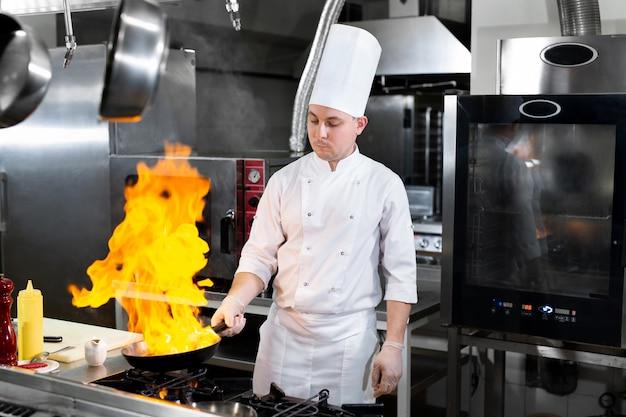 Chefkoch, der mit flamme in einer pfanne auf einem küchenherd kocht