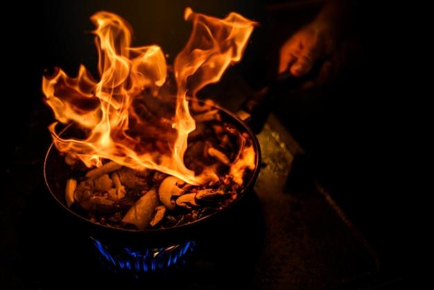 Chefkoch, der mit flammen in der eisenpfanne kocht