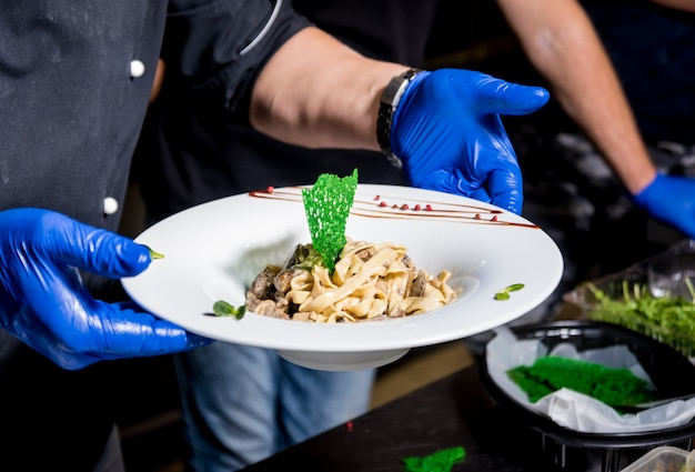 Chefkoch, der nudeln mit fleisch in der pfanne kocht. italienische küche. restaurant.