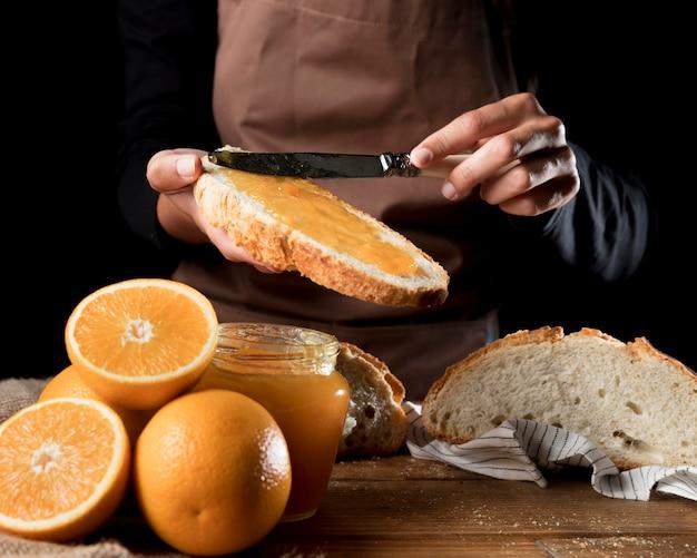 Chefkoch, der orangenmarmelade auf brot verteilt