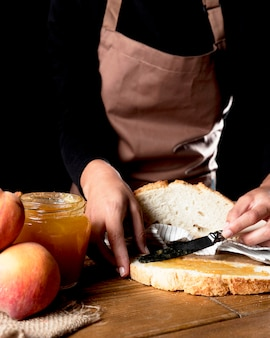 Chefkoch, der pfirsichmarmelade auf brot verteilt