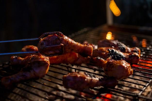 Chefkoch, der ruckgrill bbq-huhn auf der grillhand kocht, die essen dreht. gegrilltes fleisch