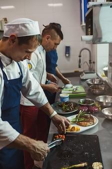 Chefkoch, der saftiges rindersteak an der restaurantküche kocht