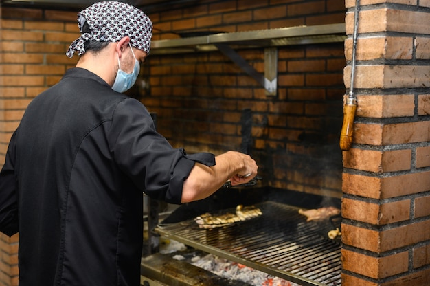 Chefkoch, der steaks in der gewerblichen küche grillt