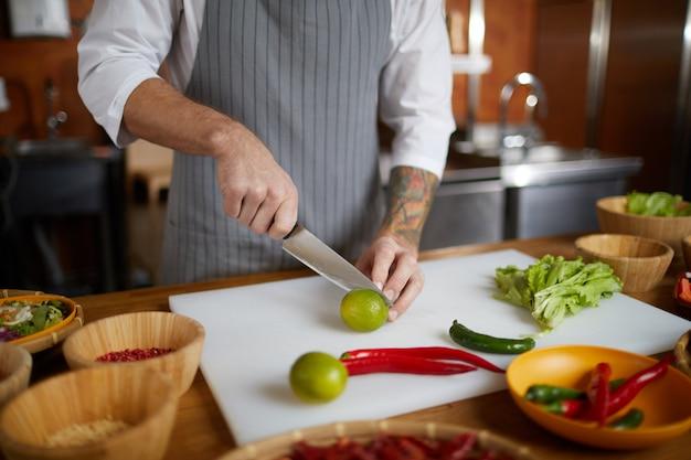 Chefkoch, der zitrusfrüchte in der küche schneidet