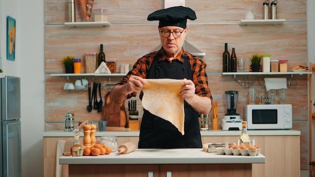 Chefkoch, der zu hause in der modernen küche handgemachte pasta mit gesunden zutaten kocht. glücklicher älterer bäcker mit knochen mit holznudelholz, bestreuen, sieben von mehl auf dem tisch, backen traditioneller kekse
