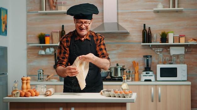 Chefkoch, der zu hause in der modernen küche teig für pizza aufwirft und vor der kamera lächelt. geschickter pensionierter älterer koch in uniform, der pizza-arbeitsplatte dreht und wirft