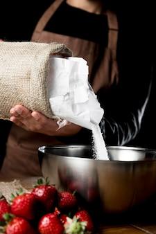 Chefkoch, der zucker in die schüssel mit erdbeeren gibt