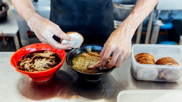 Chefkoch fügt zutaten in ramennudeln für die herstellung von miso und shoyu ramen hinzu.