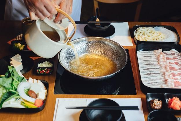 Chefkoch gießt klare shabu-brühe in silbernen topf mit kurobuta-schweinefleisch