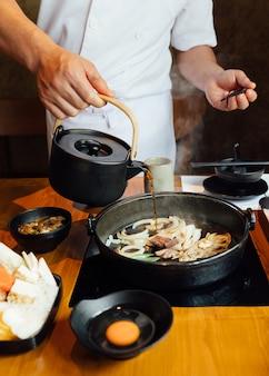 Chefkoch gießt shabu-saucenmischung mit gebratenen zwiebeln, schalotten und rinderfett.