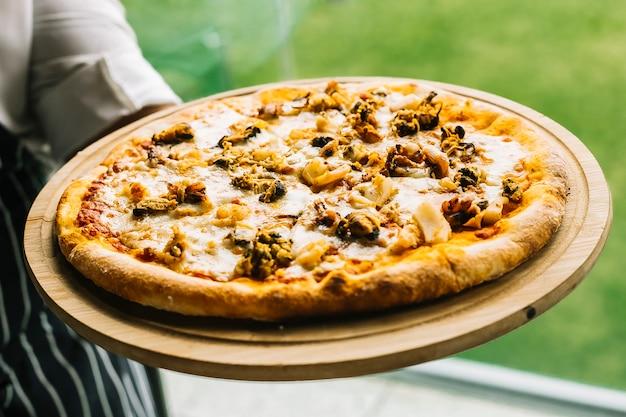 Chefkoch hält pizza mit meeresfrüchten mit garnelen, muscheln, calamari, tintenfisch und käse