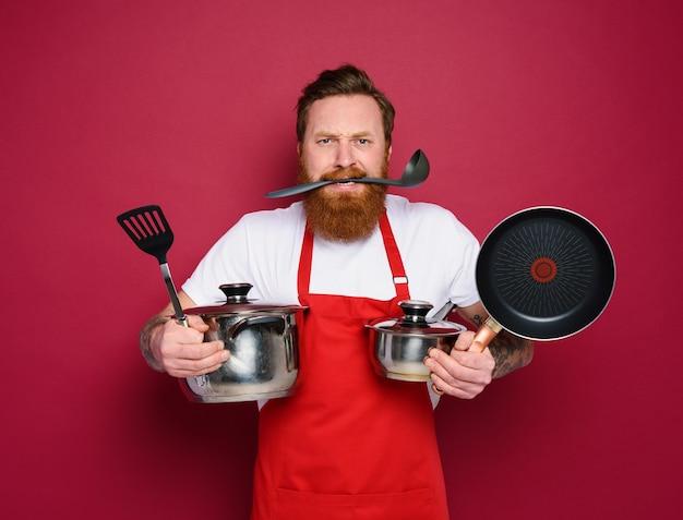 Chefkoch hält viele töpfe auf rot