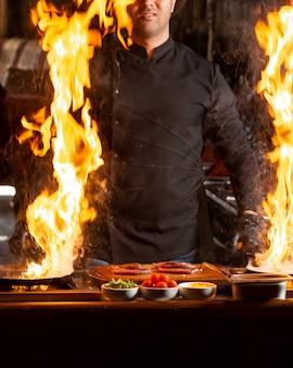 Chefkoch hält zwei pfannen mit brennendem feuer