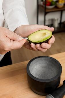 Chefkoch in der küche, die avocada kocht