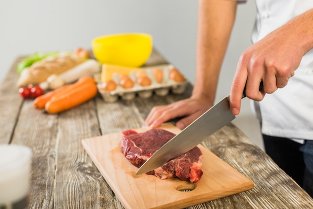 Chefkoch in der küche, die fleisch schneidet