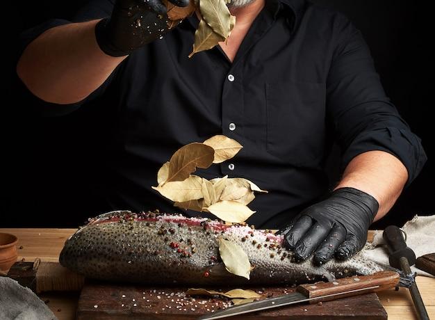 Chefkoch in schwarzer uniform und schwarzen latexhandschuhen gießt trockene lorbeerblätter auf geschnittenes frisches lachsfilet