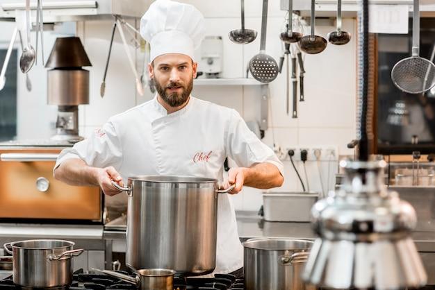 Chefkoch in uniform kochen suppe im großen herd in der restaurantküche