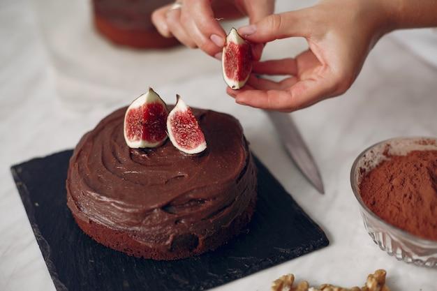 Chefkoch in weißer kleidung bereitet einen schokoladenkuchen zu. dame bereitet dessert vor. frau backt einen kuchen.