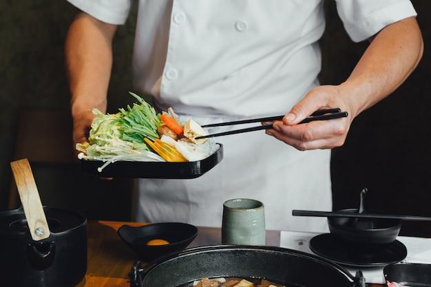 Chefkoch kneift gemüse mit stäbchen in den heißen topf, bevor er sojasuppe gießt.
