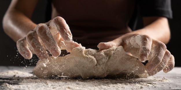 Chefkoch knetet den teig mit den mit mehl bedeckten händen