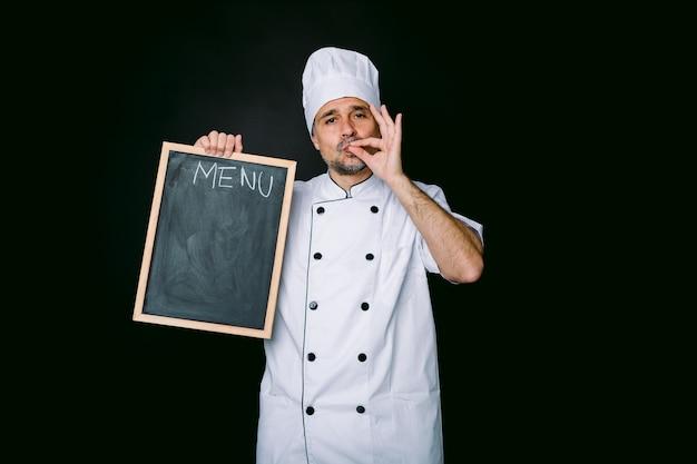 Chefkoch koch trägt küchenjacke und hut, hält eine piazarra mit der speisekarte und macht eine gute essensgeste auf schwarzem hintergrund