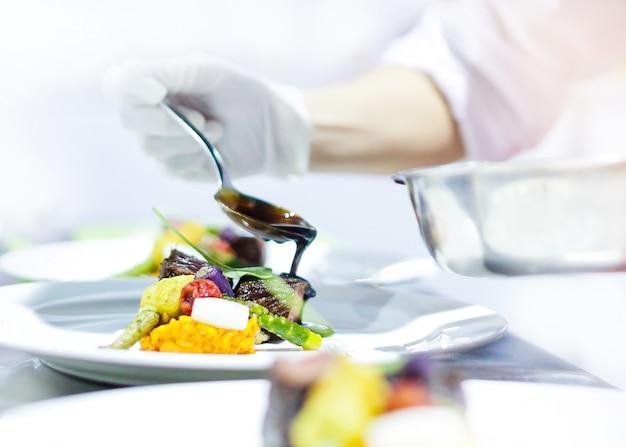 Chefkoch kocht, chefkoch, der essen in der küche zubereitet, chefkoch, der gericht verziert, nahaufnahme
