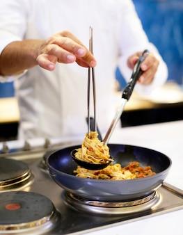 Chefkoch kocht pasta, chefkoch serviert spaghetti carbonara auf dem teller in der küche