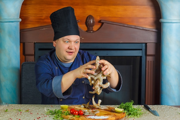 Chefkoch kocht tigergarnelen. porträt. lustiges foto.