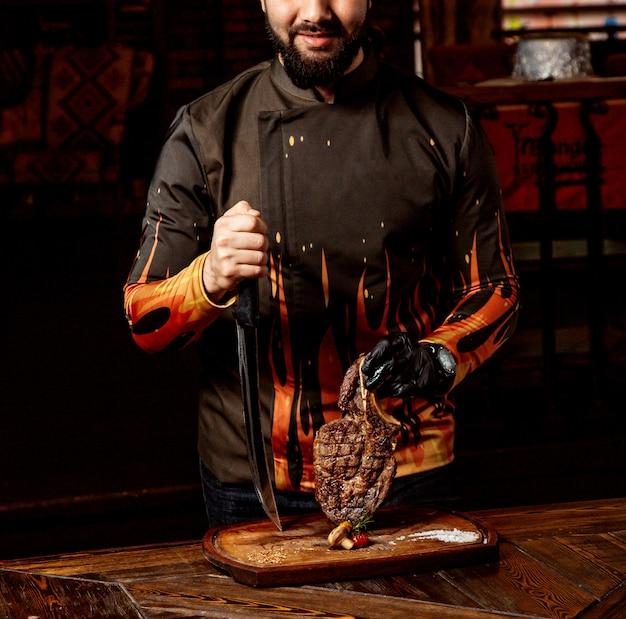 Chefkoch legt gebratenes fleisch auf das schneidebrett